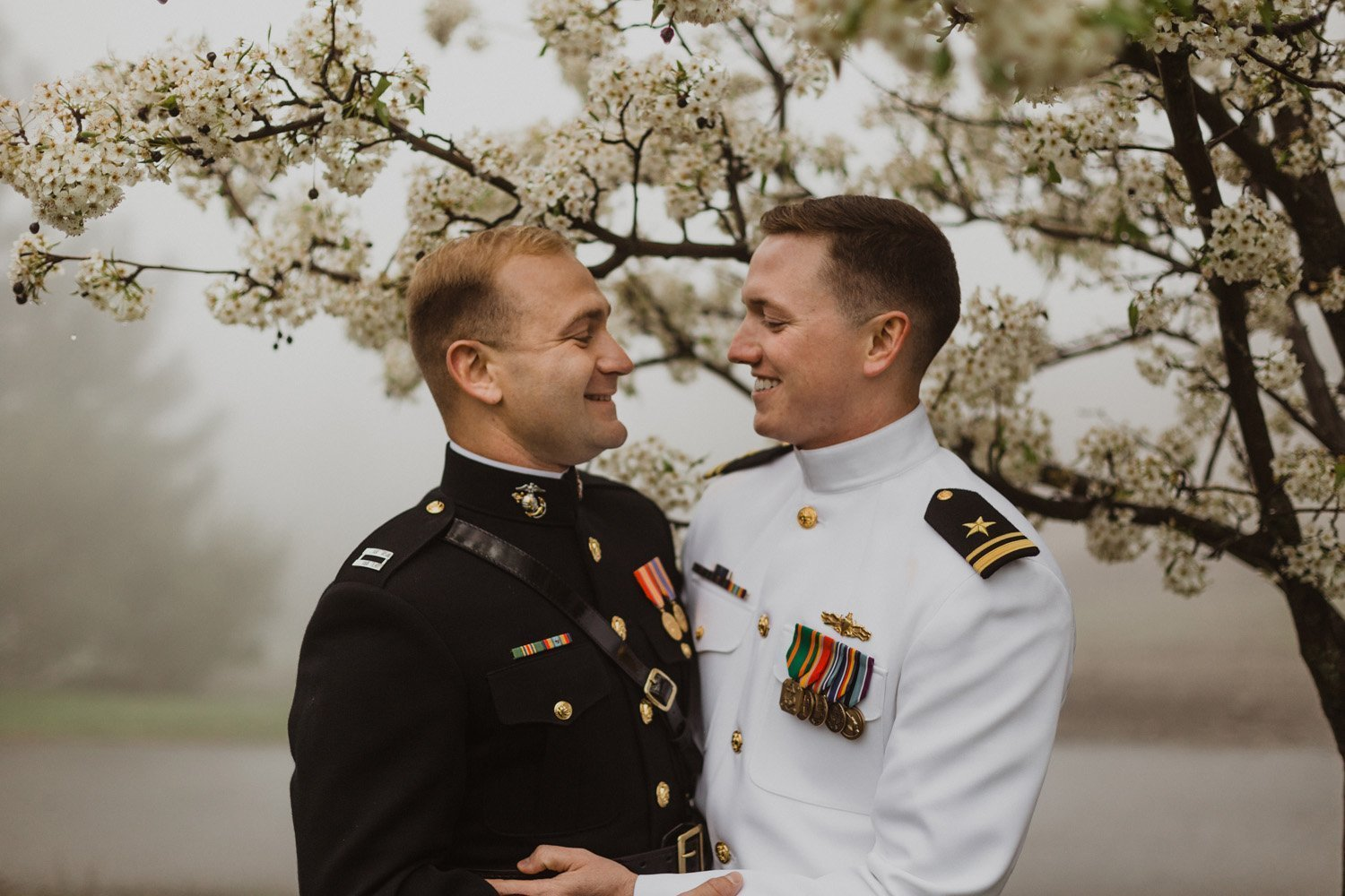 Two grooms smiling at each other under a cherry blossom tree at their Sacred Mountain Wedding in Julian, CA