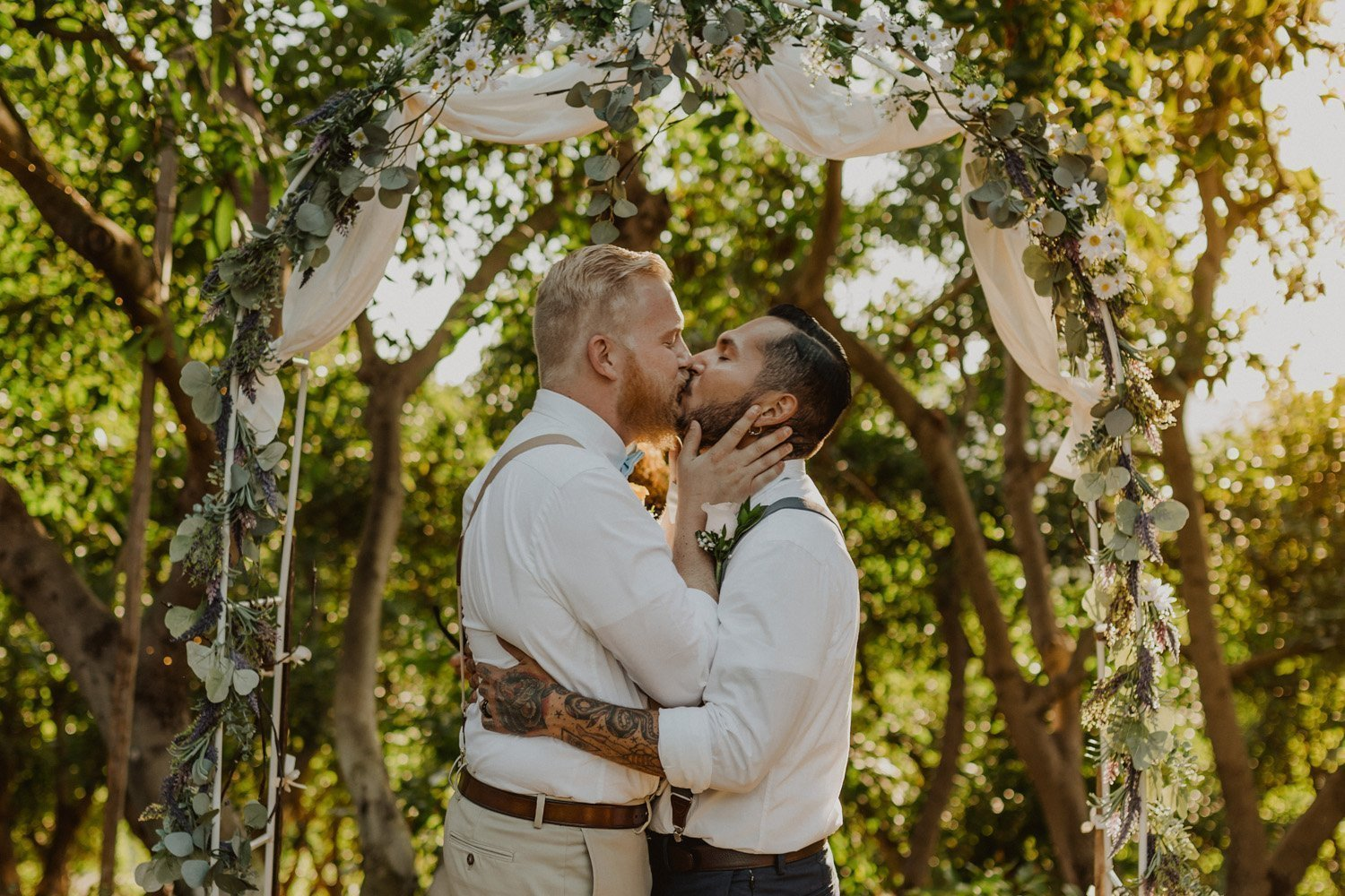 Grooms kissing during ceremony at their Valley Center avocado farm wedding