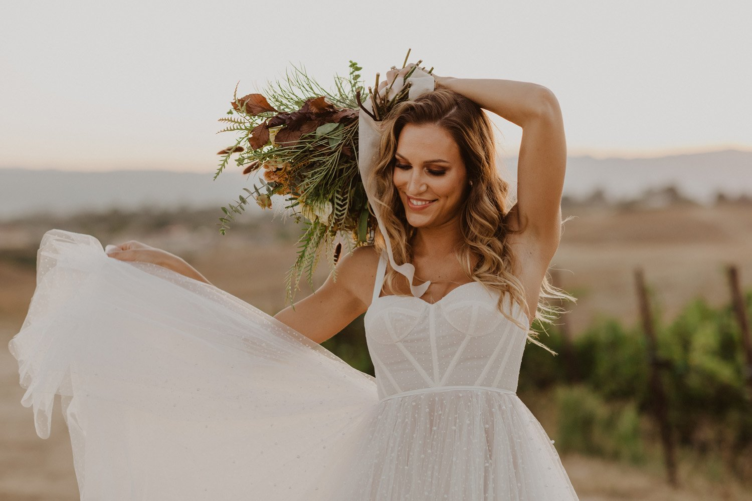 Bride holding wedding bouquet in vineyard at her Temecula bridal shoot