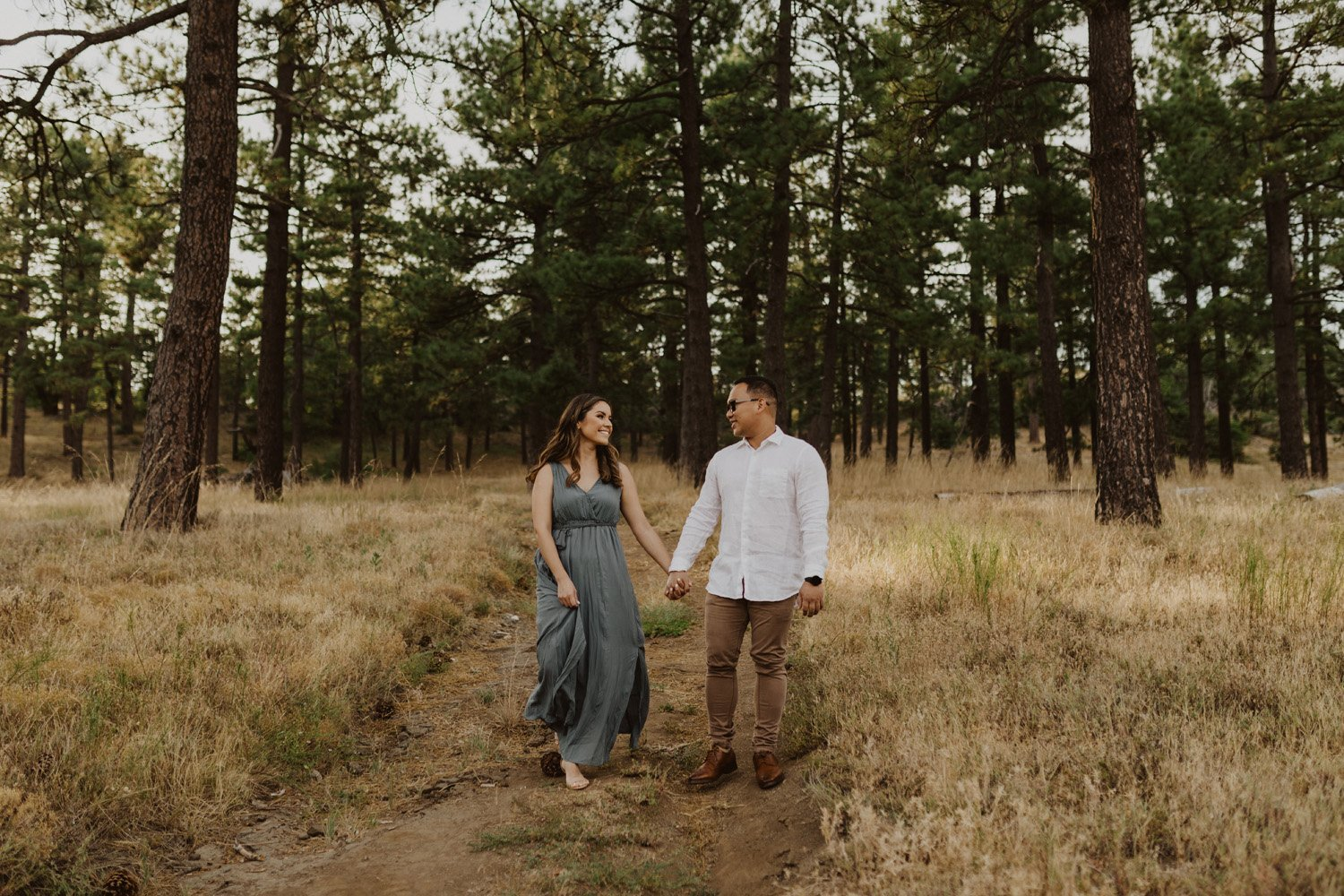 Man and woman holding hands walking through trees at their Mt. Laguna couples session