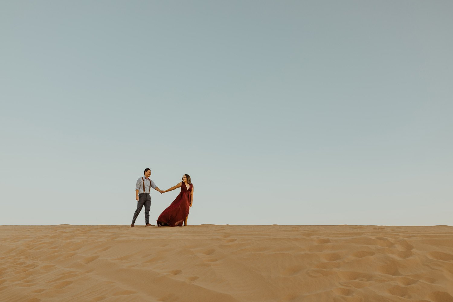 Couple holdings hands and walking at their Glamis Sand Dunes Engagement Session.