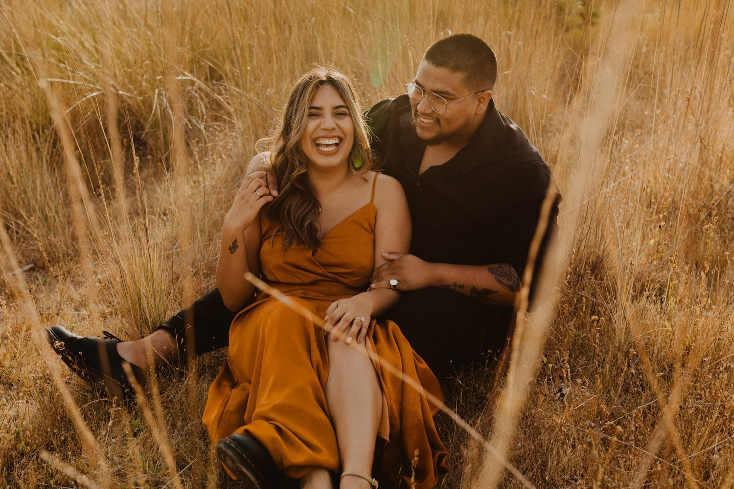 Couple laughing in golden field at their Lake Cuyamaca engagement shoot.