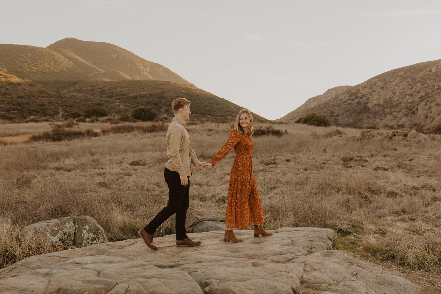 Couple holding hands walking at their Mission Trails Engagement Session.