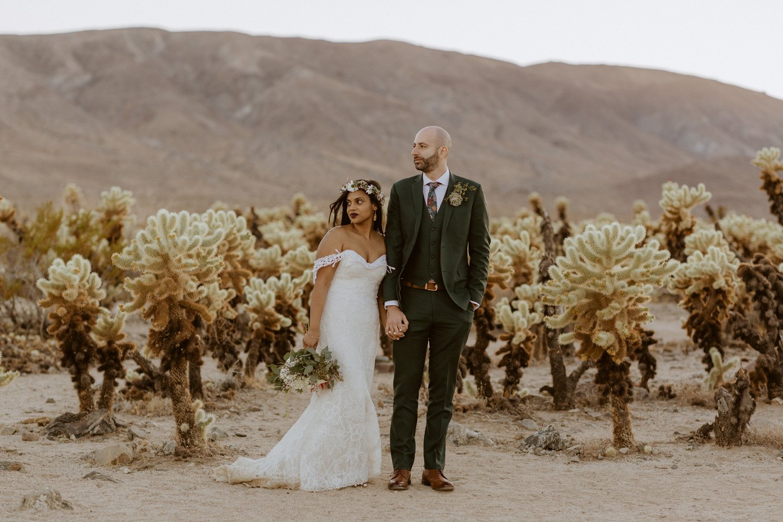 Bride and groom walking in Chollas cactus garden at their Joshua Tree wedding