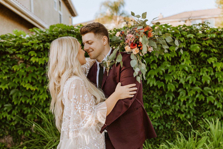 Bride and groom holding hands at their Murrieta backyard wedding.