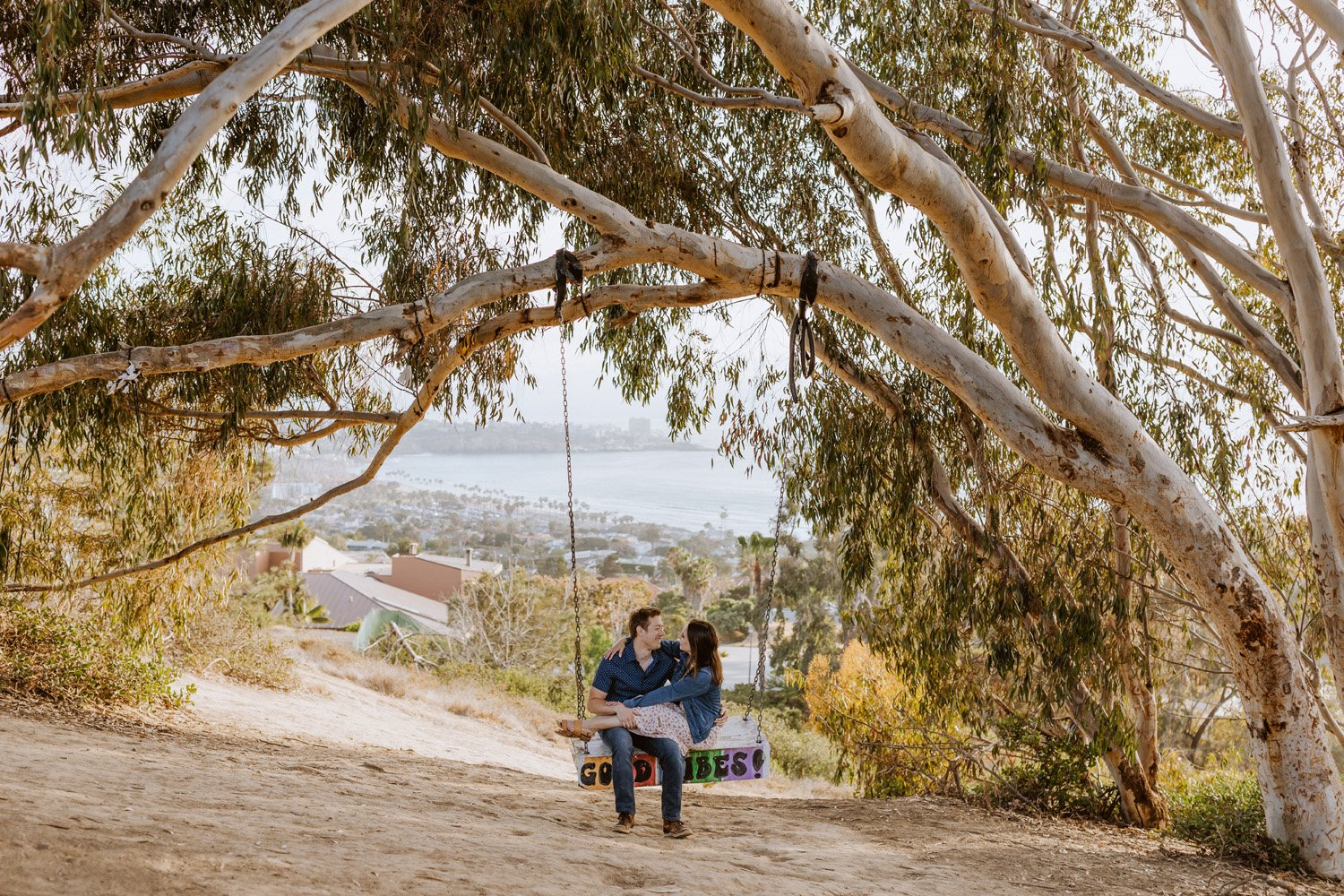 Couple cuddling on swing at their La Jolla Shores engagement session.